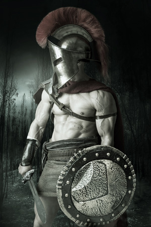 Ancient warrior or Gladiator posing in a dark forest