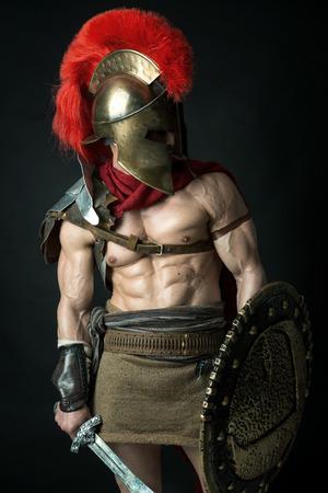 Oude krijger of Gladiator poseren op een donkere achtergrond Stockfoto