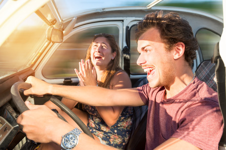 Couple in a car at sunset, with male driving fast and girl scared, screaming and praying. Stock fotó