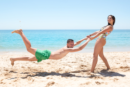 Young couple playing and having fun at the beach.