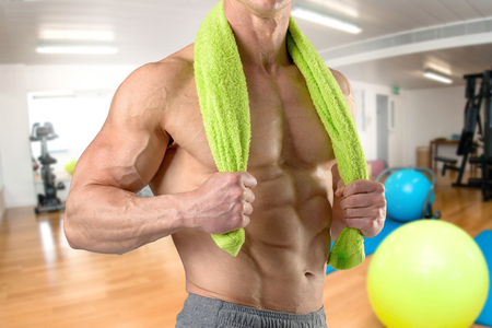 Powerful athletic man with great physique holding a towel in the gym Banco de Imagens