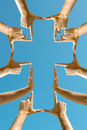 Hands forming a cross against the blue sky