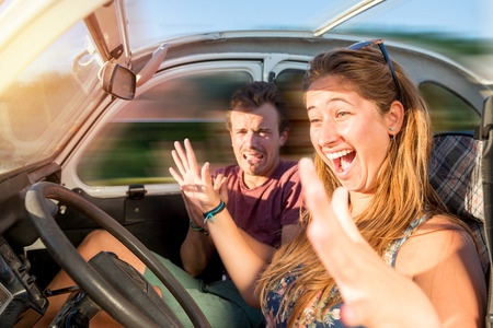 Couple in a car at sunset, with girl driving with no hands and boy scared, screaming and praying. Stock Photo - 89520687