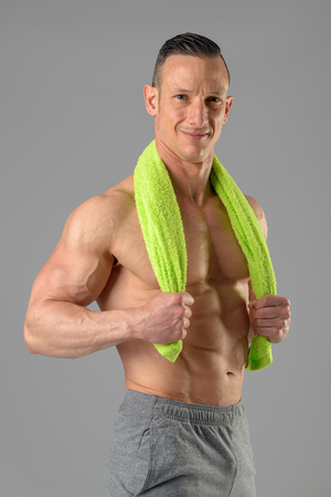 Powerful athletic man with great physique holding a towel.