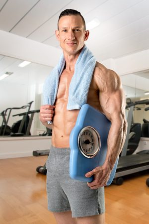 Powerful athletic man with great physique holding a weight scale in the gym