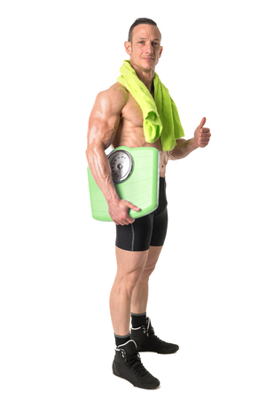 Powerful athletic man with great physique holding a weight scale and towel.