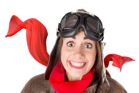 Funny girl with freckles wearing helmet, goggles and a red scarf