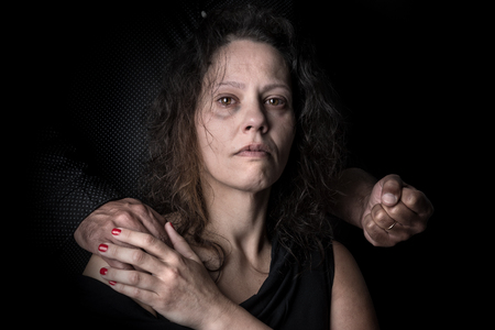 Abused woman victim of domestic violence, with mans fist.