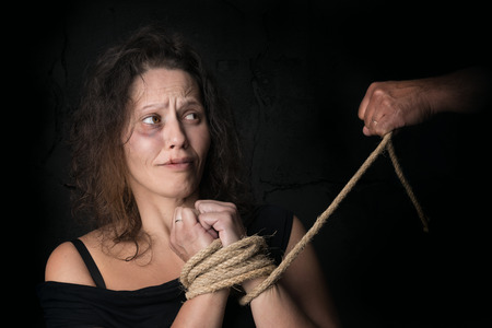 Abused woman victim of domestic violence tied with rope Banco de Imagens