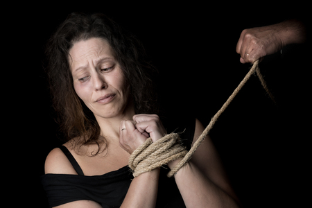 Abused woman victim of domestic violence tied with rope Stock Photo