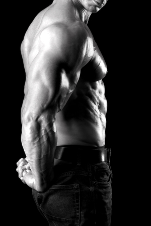 Muscled male body part with arms and torso isolated in black Stock Photo