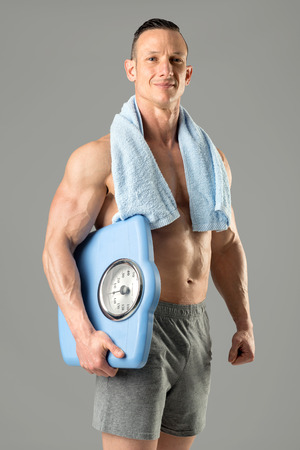 Powerful athletic man with great physique holding a weight scale.