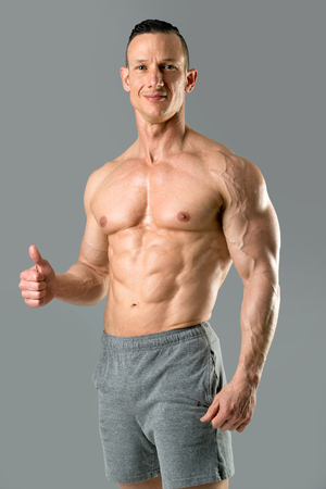 Powerful athletic man with great physique in gray background.