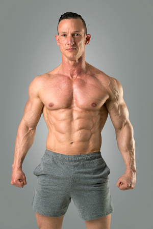 Powerful athletic man with great physique. Strong bodybuilder with six pack, perfect abs, shoulders, biceps, triceps and chest. 写真素材