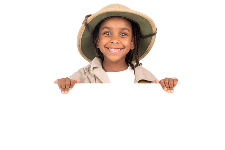 Young girl with Safari clothes behind a white board isolated in white