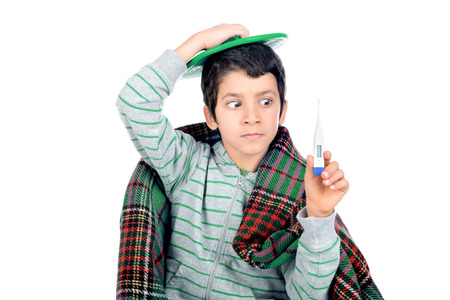 Young boy with a cold wrapped in a blanket with a termometer Stockfoto