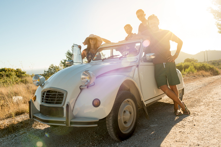 Group of happy people near a car in summertime, retro style. Stock Photo