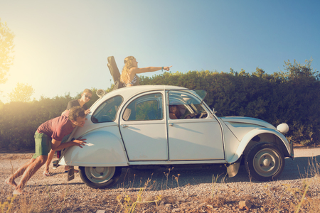 Guys pushing a broken old car with girls at the wheel during vacations. Stock Photo