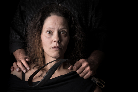 Abused woman victim of domestic violence, with husband hand holding a belt as a weapon.