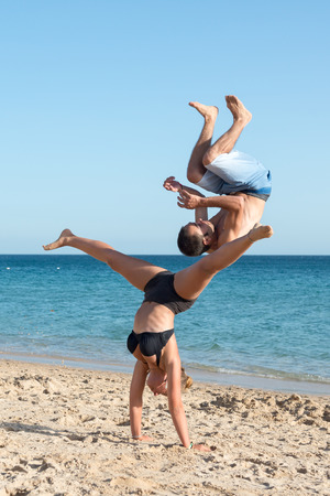 Couple having fun doing jumps in the beach