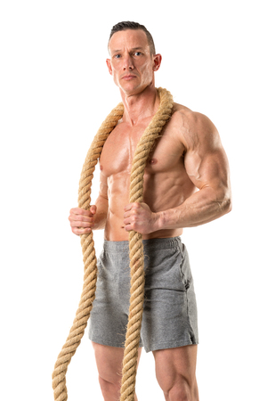 Power athletic man with great physique. Strong bodybuilder holding a big rope.
