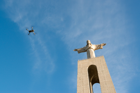 Statue of Cristo Rei in Almada, over Tagus river with a drone passing by.