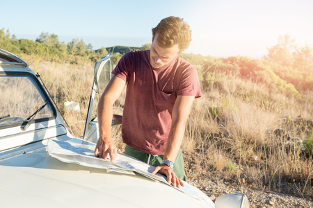 Vintage style image of a man looking at a map over a car in countryside.
