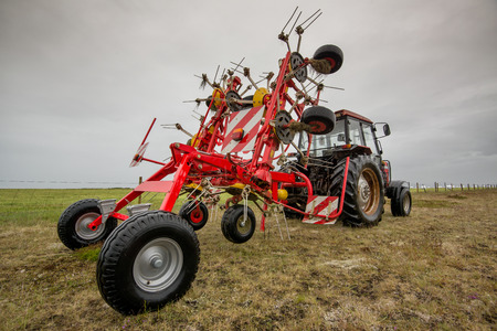 Red tractor in the field with a cloudy sky