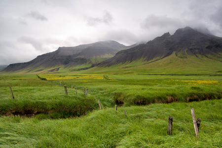 Beautiful landscape of Icelandic field with fence and mountain 스톡 콘텐츠 - 104488029