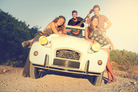 Group of happy people in a car at sunset in summer.