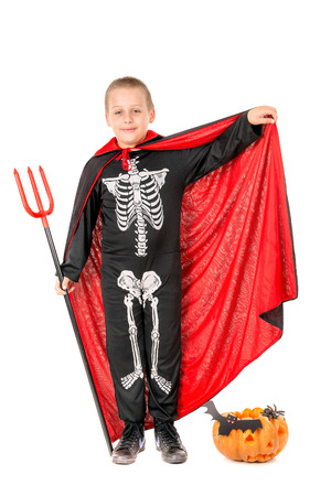 Boy in Halloween costume with pumpkin over a white background