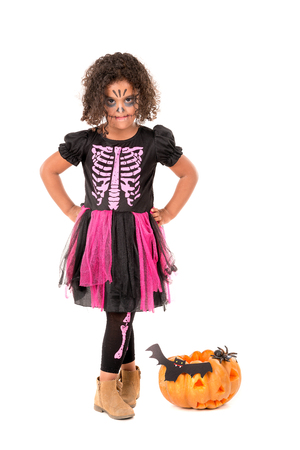 Girl in Halloween witch costume with pumpkin over a white background
