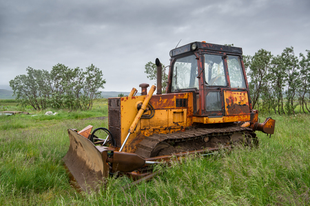 Old bulldozer abandoned in a grass field in a stormy day Stockfoto