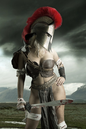 Ancient woman warrior or Gladiator posing outdoors with sword and helmet