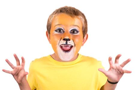 Niño con pintura facial de león detrás de una pizarra blanca
