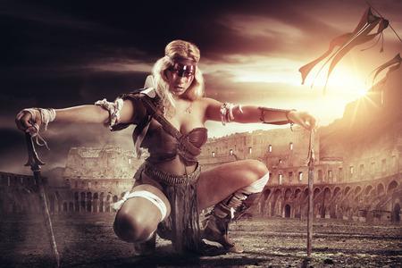 Alte Kriegerin oder Gladiatorin in der Arena mit Schwertern