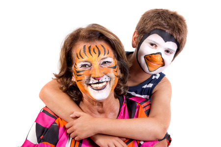 Boy with grandmother with animal face-paint isolated in white