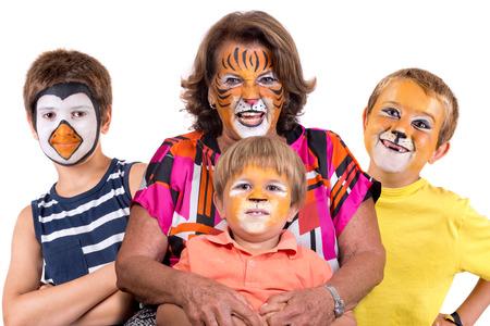 Grupo de niños y abuela, todos con pintura facial de animales aislados en blanco