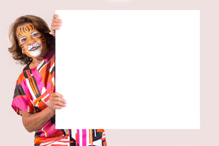 senior woman with tiger face-paint over a white board isolated in white