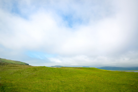 Beautiful view of icelandic green fields with cloudy skies Stock Photo