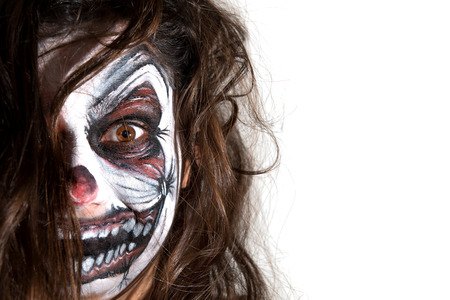 Teenage girl with scary clown face painting