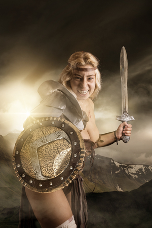 Ancient woman warrior or Gladiator posing outdoors with sword and shield