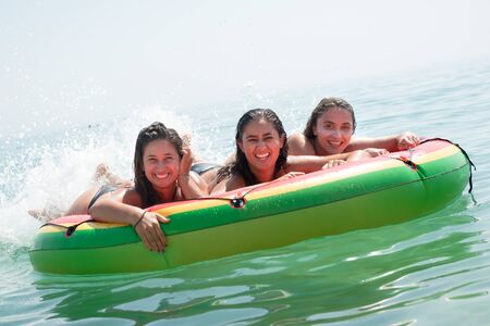 Happy girls in an inflatable watermelon at the beach