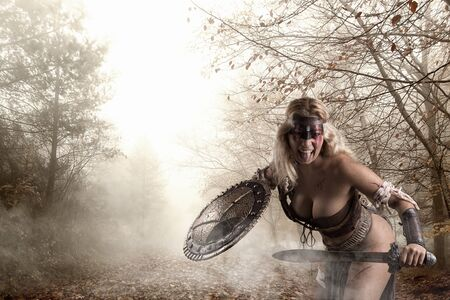 Ancient woman warrior or Gladiator posing outdoors with sword and shield Stock Photo
