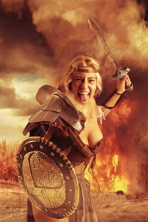 Ancient woman warrior or Gladiator in a burning forest fighting with sword and shield
