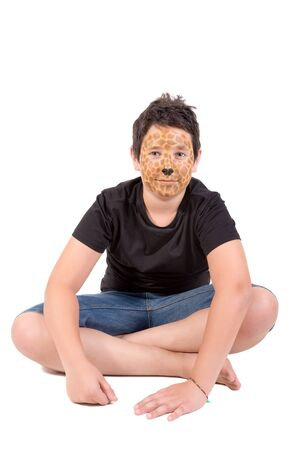 Boy with giraffe face-paint behind a white board