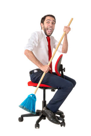 Businessman rowing with a broom in a office chair isolated in white Zdjęcie Seryjne