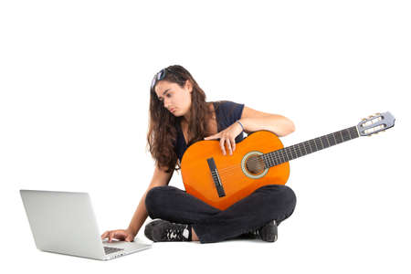 Happy girl posing with guitar and laptop, isolated in white Zdjęcie Seryjne