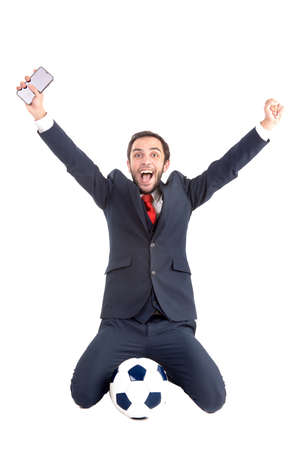 Happy businessman with soccer ball and phone posing isolated in white
