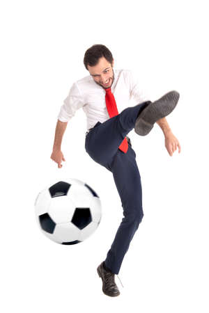 Businessman kicking a soccer ball isolated in white